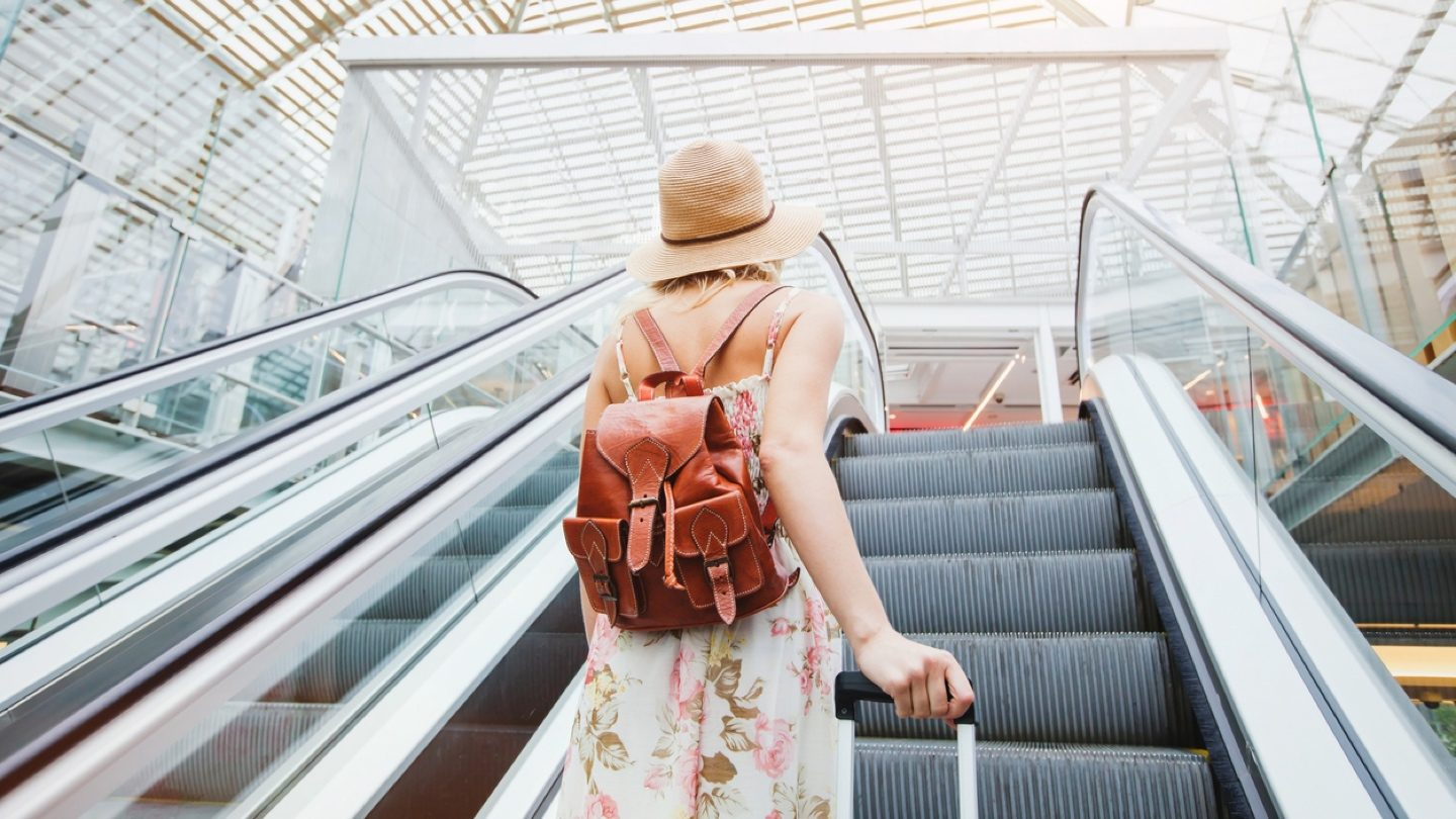 Woman going up the escalator at the airport