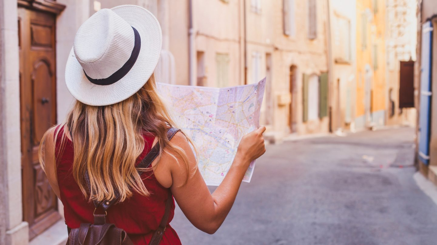 woman in hat travelling the world using personal loan