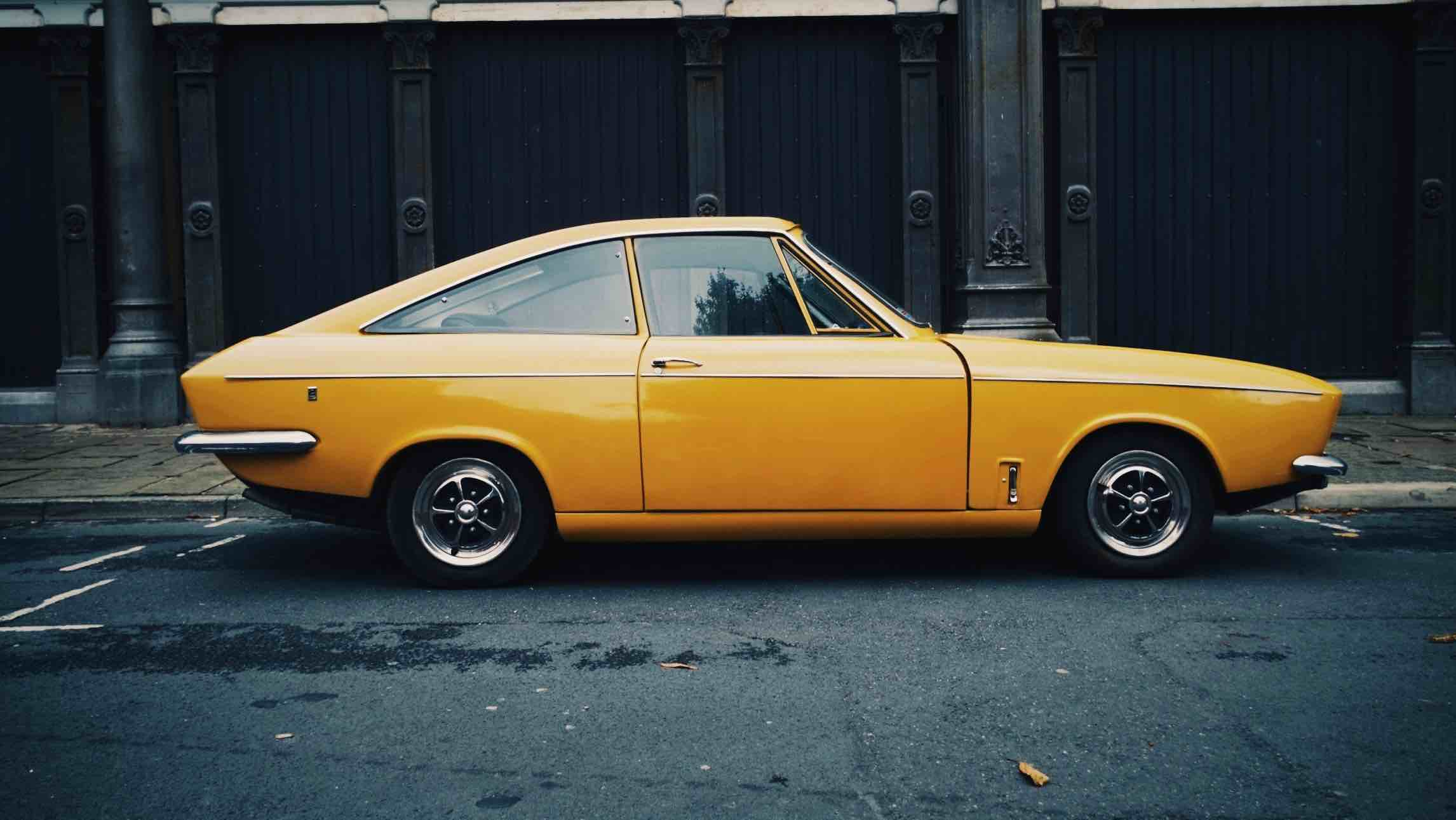 Yellow vintage car parked on street kerb with car insurance.