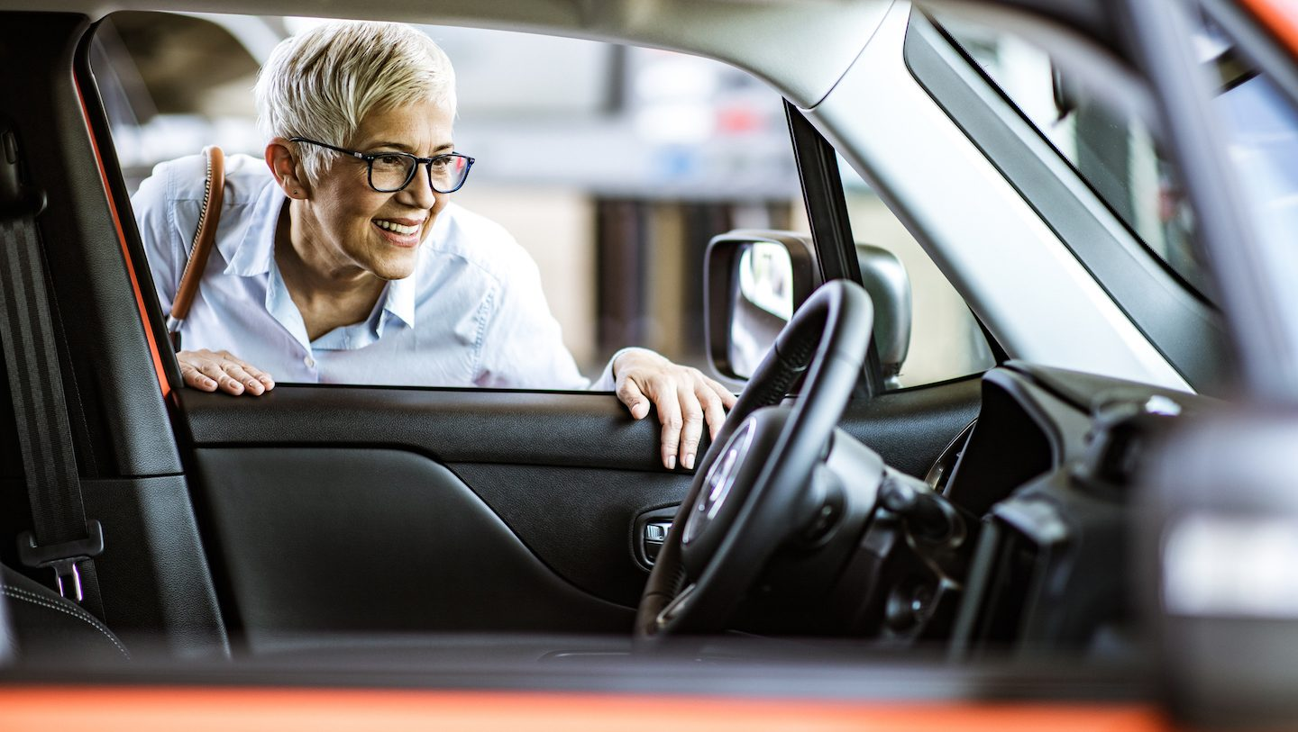 woman looking inside car determining what she can afford