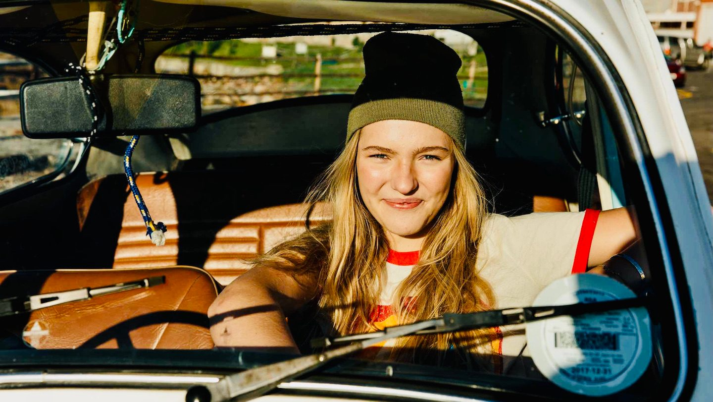 Person smiling in older car, with cheap car insurance