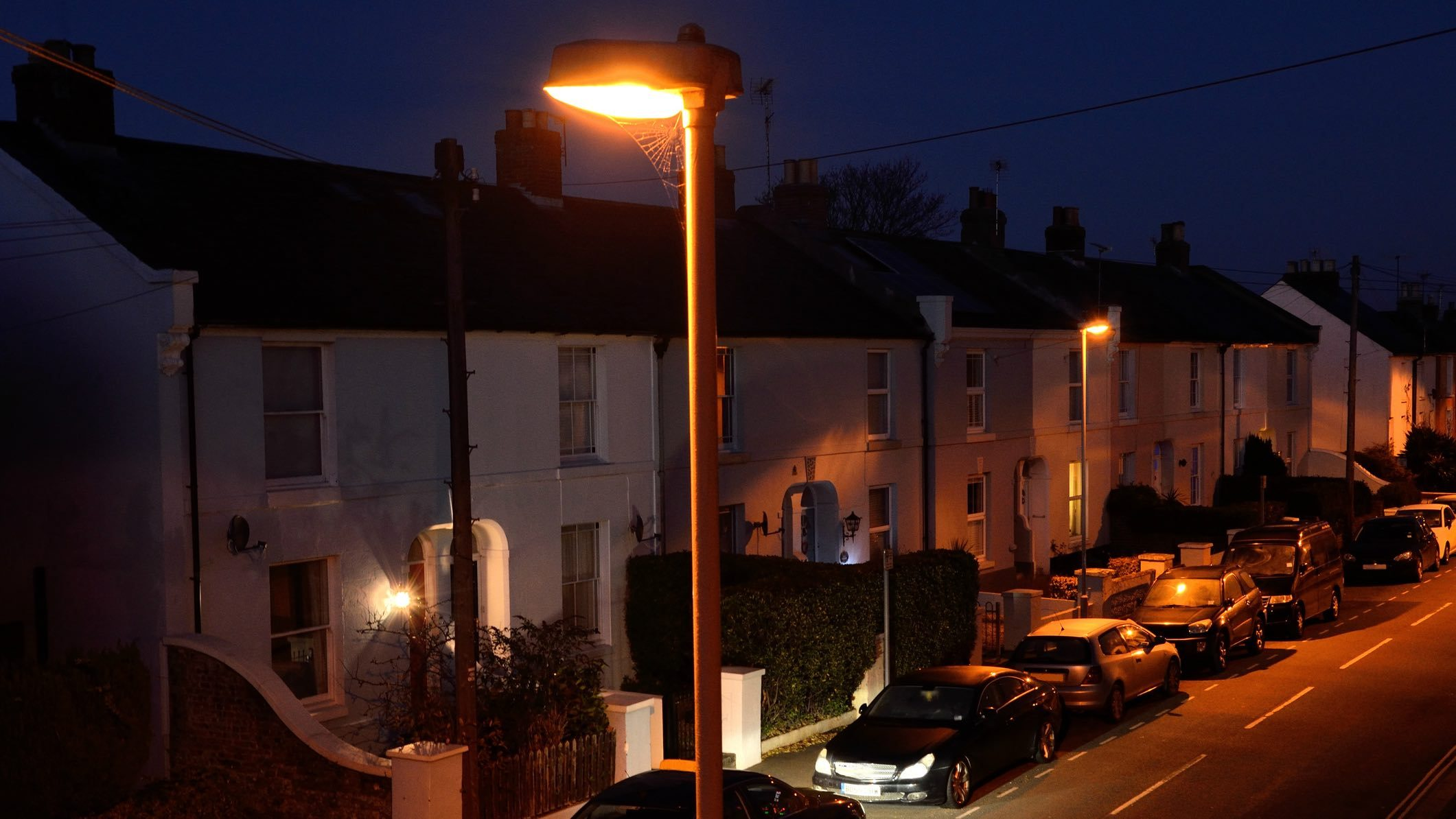 Cars parked on a suburban street at night which might require fire and theft car insurance.