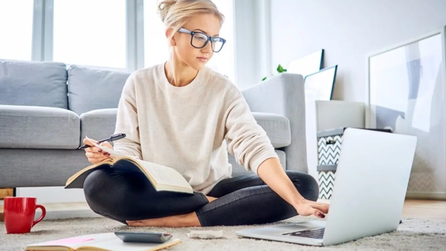 Woman sitting on the floor looking at computer and calculator as she does compound interest calculations.