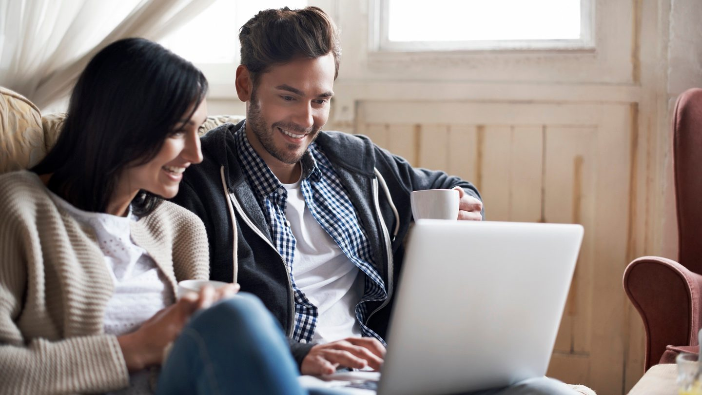young couple searching for types of personal loans on laptop