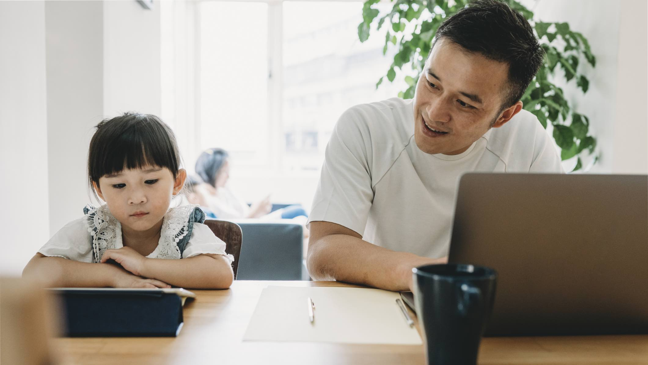 Parent and child looking at computers, considering life insurance.