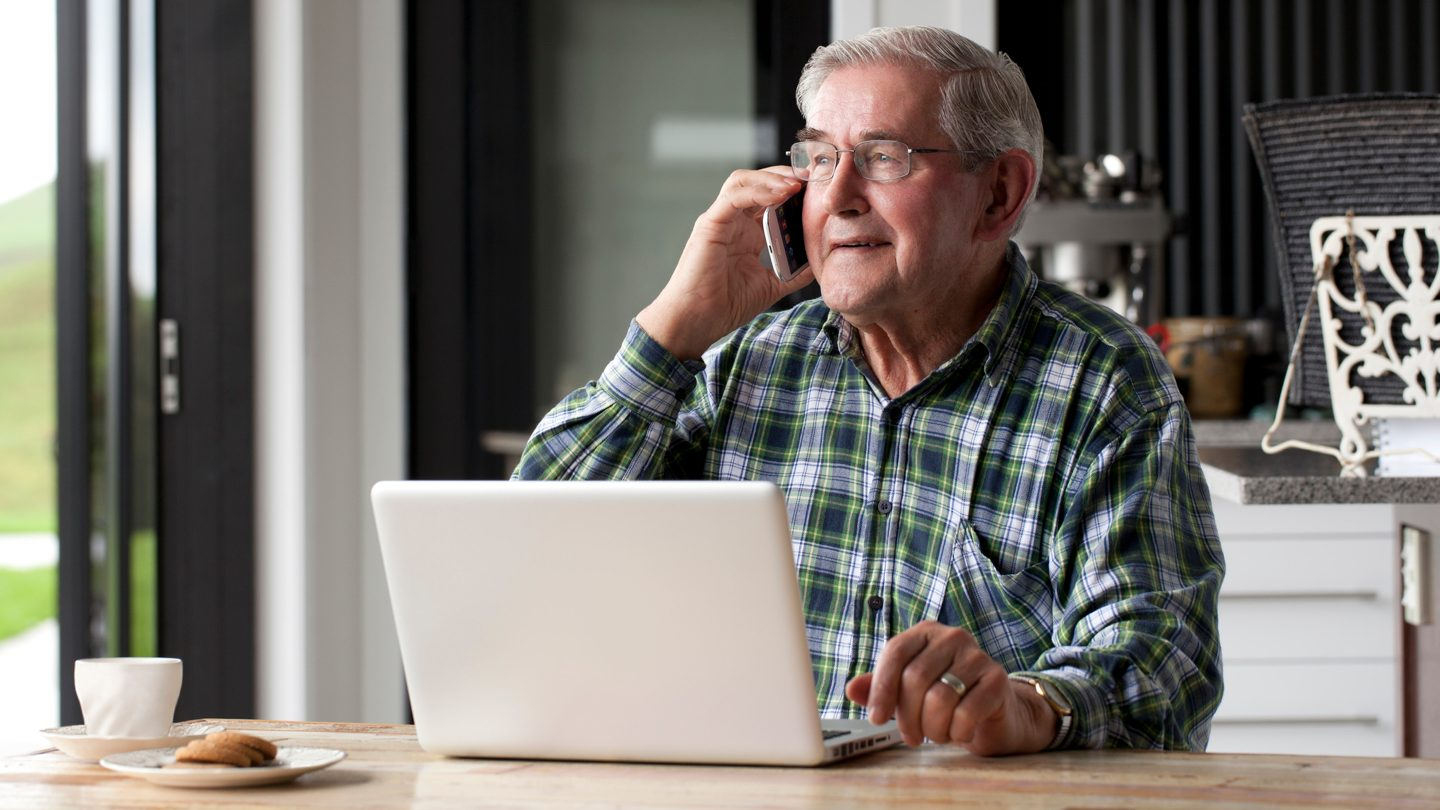 old-man-on-laptop-and-phone-government-support
