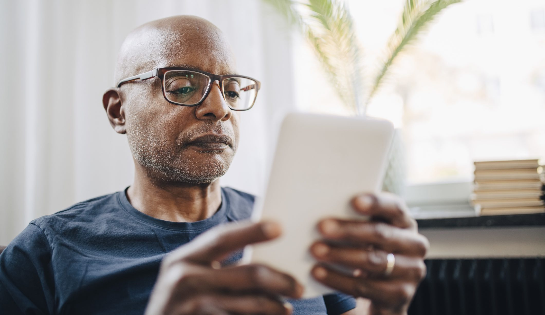 Older man researching insurance on a tablet device.