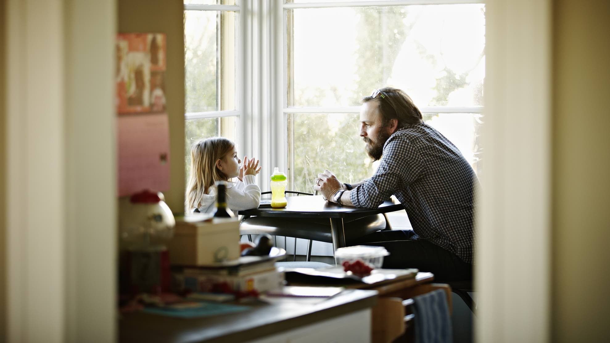 Father and child sitting at table, thinking about life insurance.