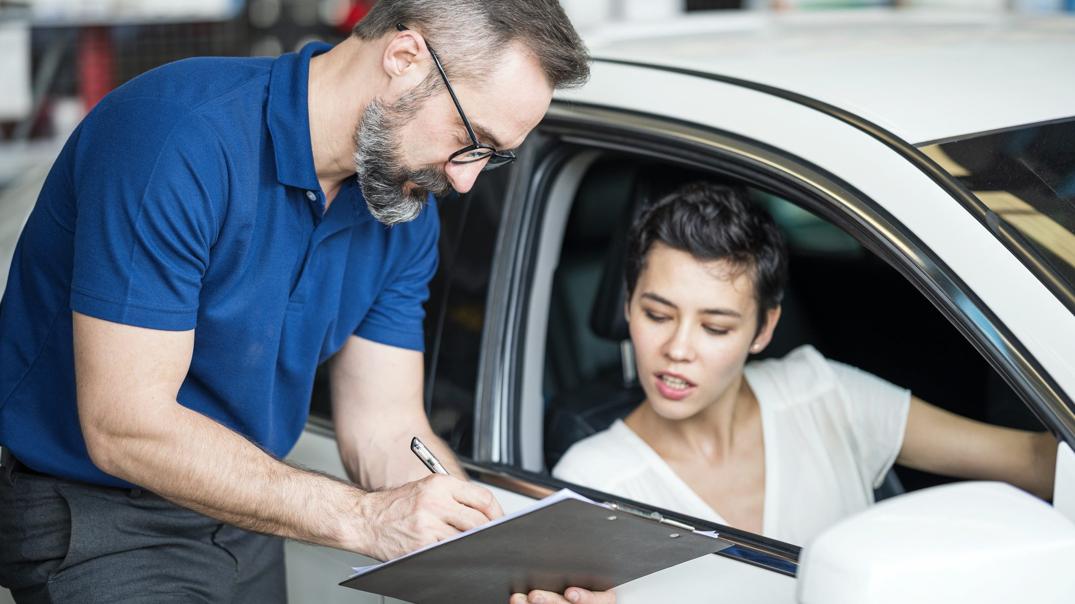 Person in car looking worried at at life insurance documents offered by salesperson.