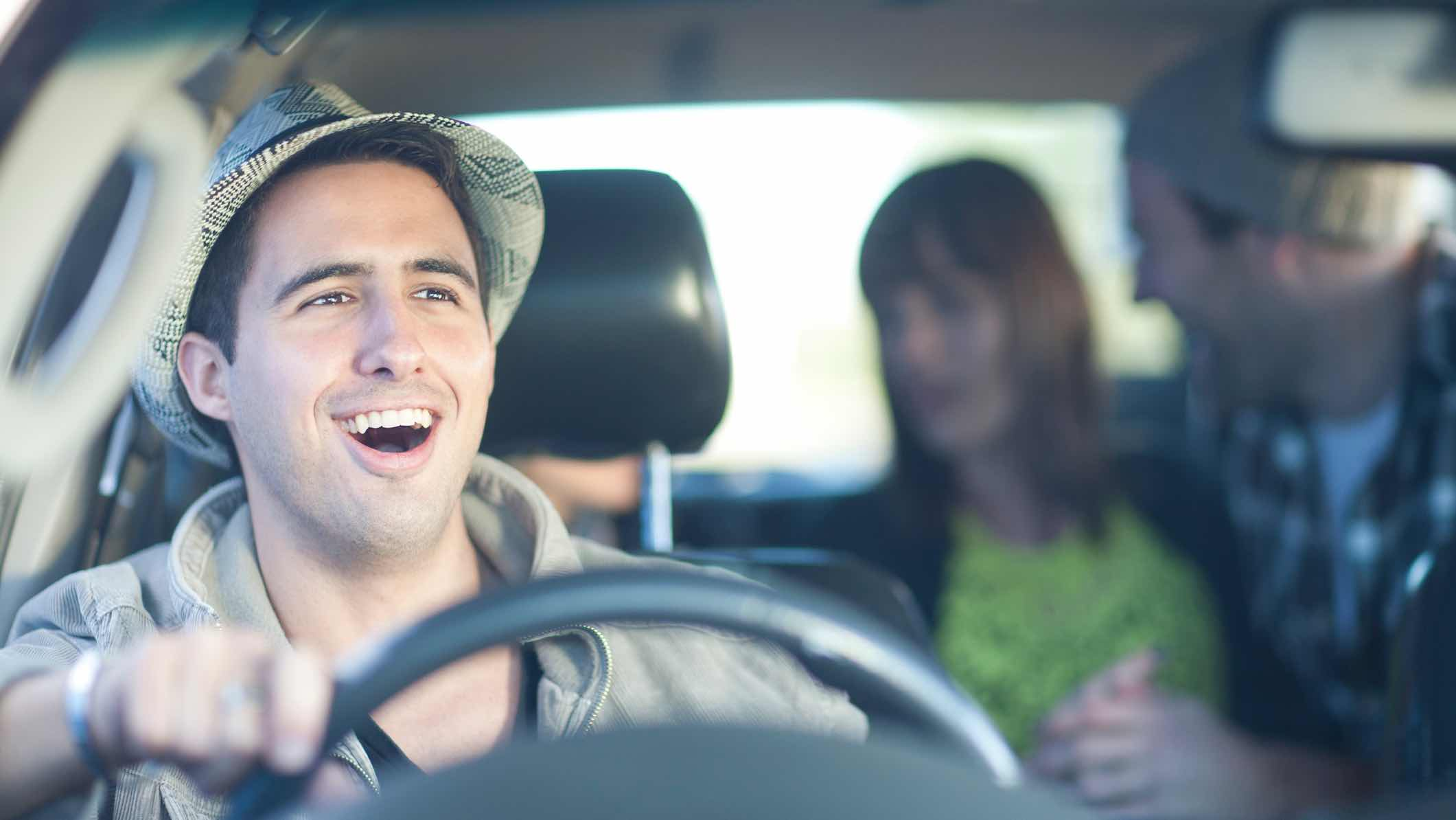 People smiling and driving in a car when a friend has borrowed the vehicle.