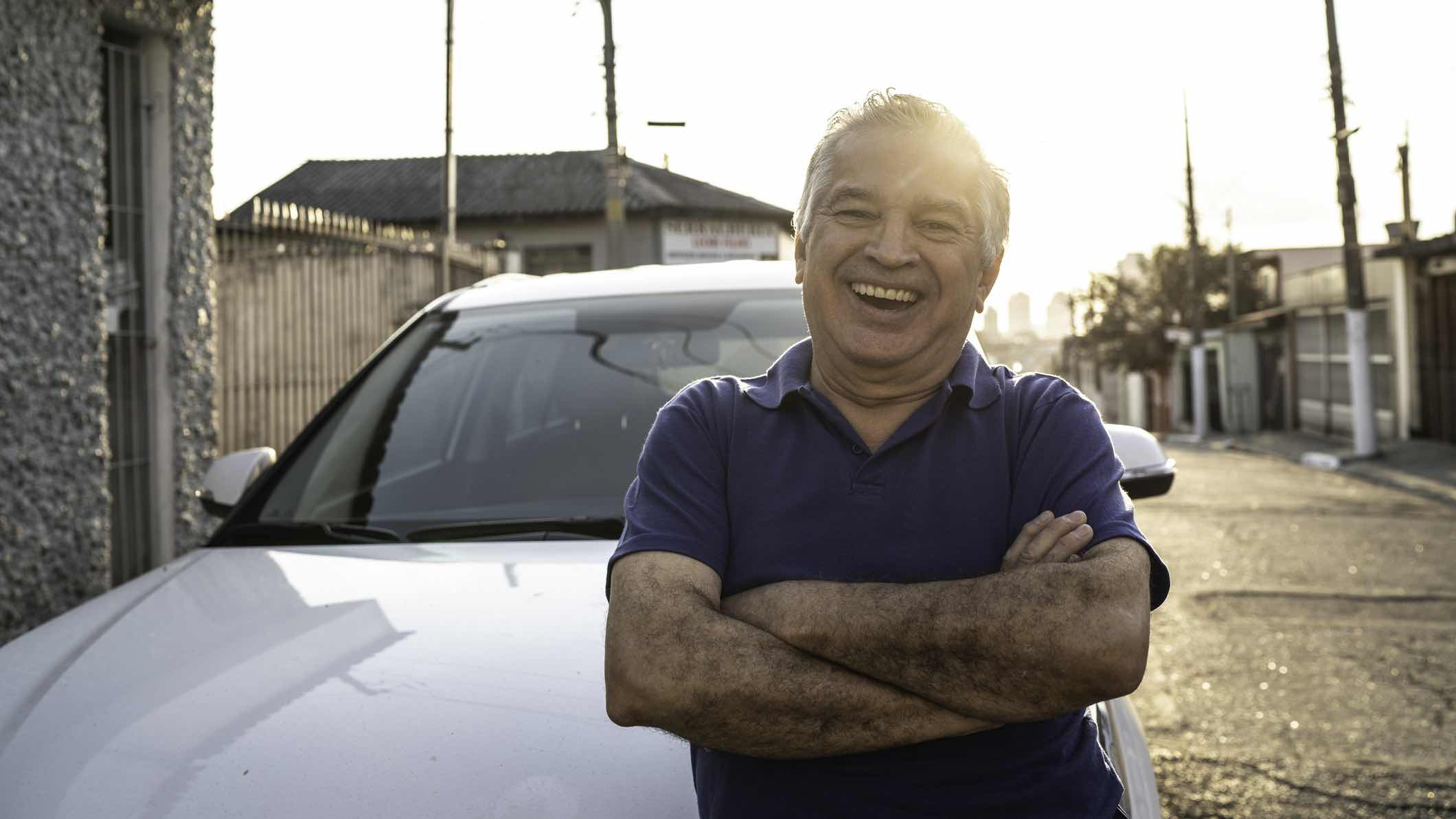 Man smiling in front of car with insurance