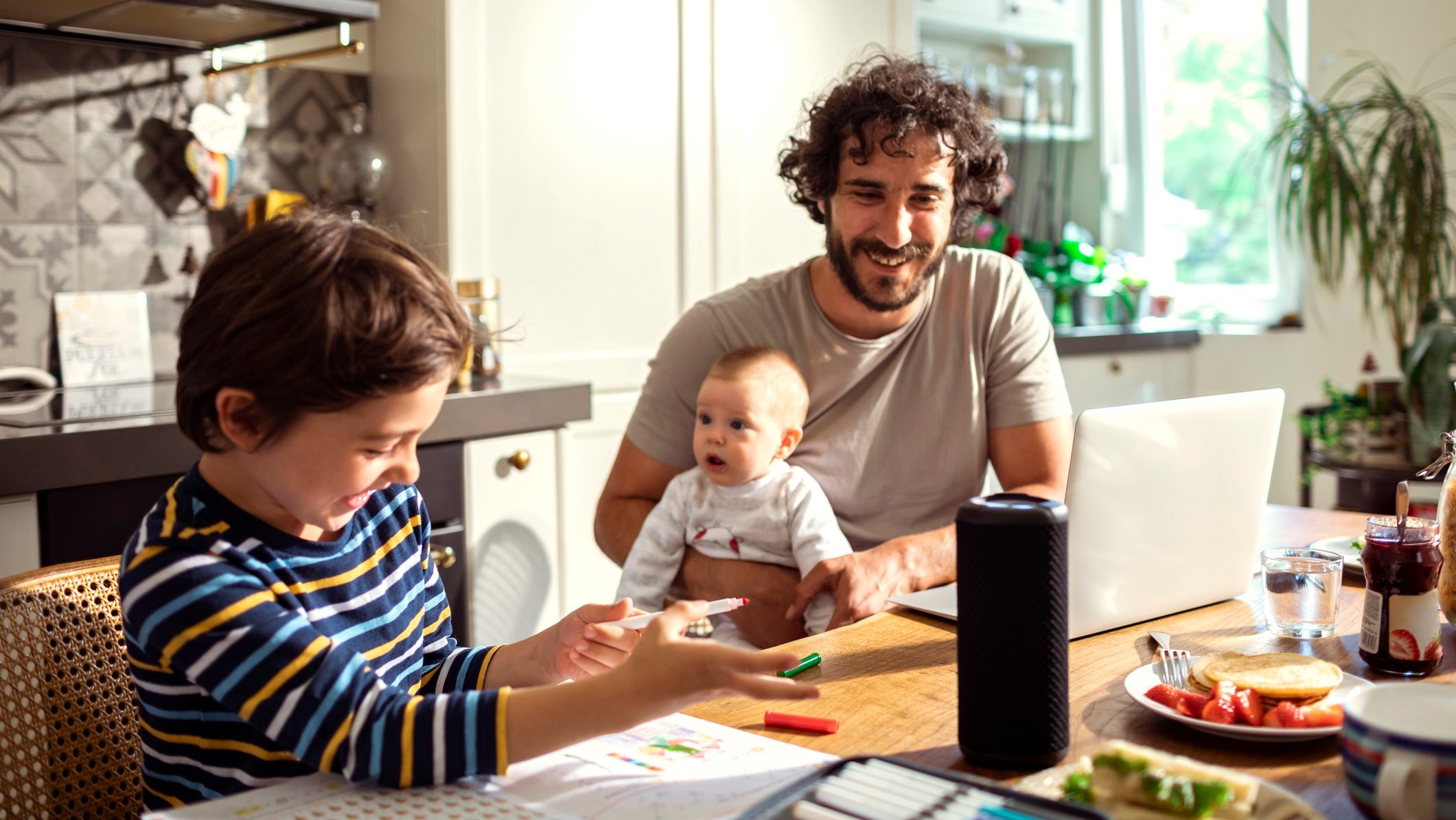 Family sitting at kitchen table, with smart home technology for insurance.