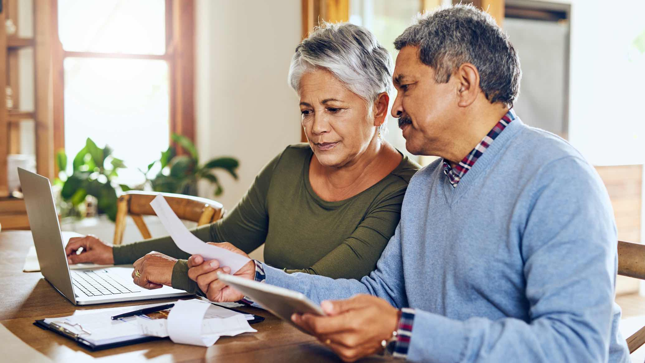 Older couple looking at bills, considering different bank accounts.