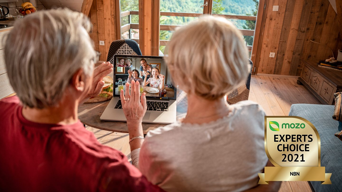 Older man and woman video chat with family on laptop.