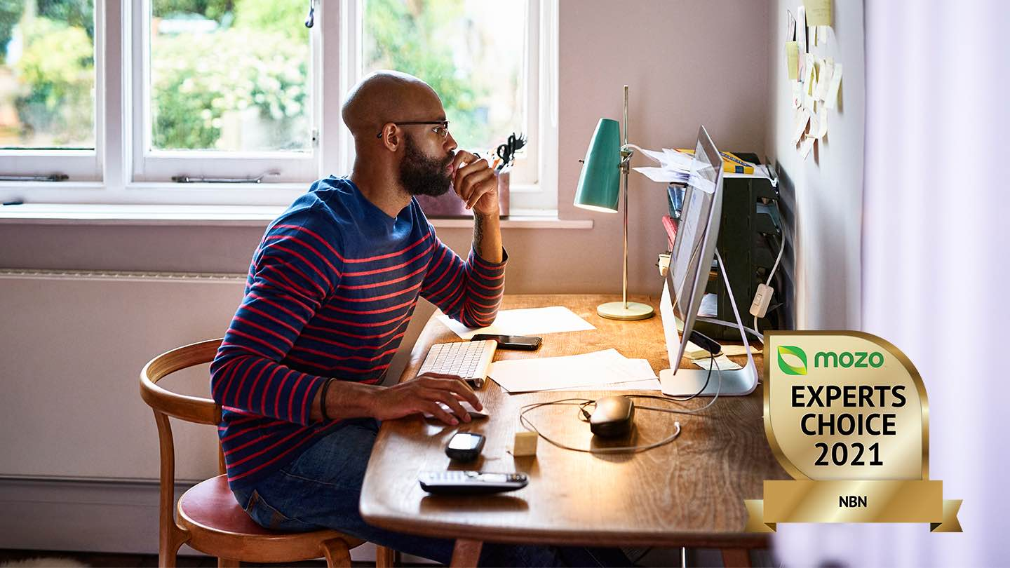 Man sits at desk, in front of computer.