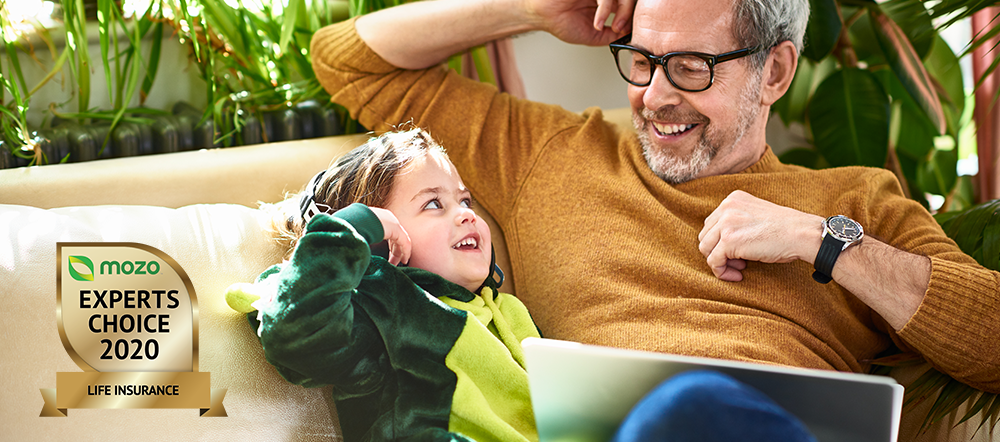 Man and little girl sitting on sofa looking at NRMA life insurance on laptop.